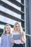 2 белокурых друз студентов смеясь над используя мобильный телефон и таблетку Стоковые Изображения RF