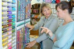 Белошвейка выбирая потоки на магазине Стоковое Изображение