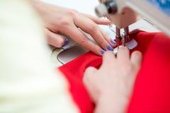 Белошвейка девушки шьет на швейной машине Стоковые Изображения RF