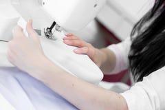 Белошвейка девушки шьет на швейной машине Стоковые Фото