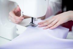 Белошвейка девушки шьет на швейной машине Стоковое Фото