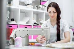 Белошвейка девушки шьет на швейной машине стоковая фотография rf