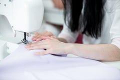 Белошвейка девушки шьет на швейной машине Стоковые Изображения