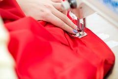 Белошвейка девушки шьет на швейной машине Стоковое Изображение RF