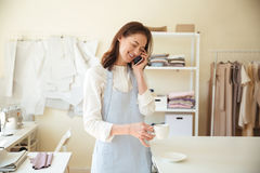 Белошвейка женщины говоря на телефоне и выпивая кофе Стоковая Фотография