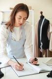 Белошвейка женщины Cocentrated в голубой рисберме рисуя новое scetch Стоковое Изображение