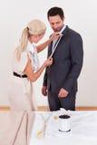 Белошвейка измеряя человека для костюма стоковые изображения rf