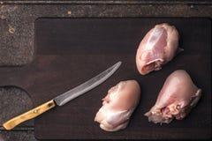Бедренная кость цыпленка без кожи и без косточек на деревянной доске Стоковое фото RF