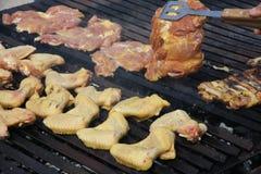 Крыла и куриные грудки сваренные в гигантском барбекю в Гаре Стоковое фото RF