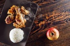 Бедренные кости цыпленка на яблоках с белым рисом, едой на деревянном столе, фотографии продукта для ресторана Стоковые Фотографии RF