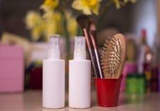 Белые бутылки для косметики брызга с щеткой на backgroun нерезкости стоковые изображения
