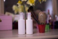 Белые бутылки для косметики брызга с щеткой на backgroun нерезкости стоковые изображения rf