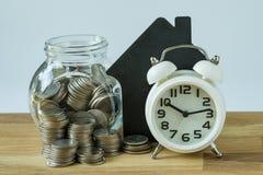 Белые будильник и стог монеток и монеток в стеклянном опарнике с Стоковые Изображения
