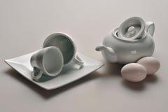 Белые блюда от китайского фарфора: чайник с поднятой крышкой, 2 чашками, поддонником, рядом с яичками цыпленка лож 2 чайника розо Стоковая Фотография RF