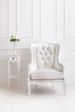 Белые винтажные кресло стиля и ваза цветков на столе Стоковое фото RF