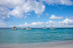 Белые высокоскоростные шлюпки стоят на банке карибского моря, обозревая красивое небо с белыми облаками Стоковые Изображения RF