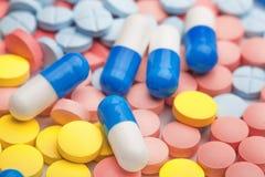 Белые и голубые пилюльки на предпосылке покрашенных медицинских пилюлек Стоковое Изображение RF