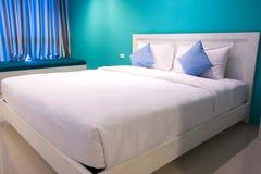 Белые и голубые подушки на нежности кровати удобной Стоковые Фотографии RF