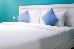 Белые и голубые подушки на нежности кровати удобной Стоковое Фото