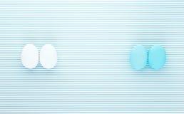 Белые и голубые яичка на горизонтальной предпосылке нашивки Стоковая Фотография RF