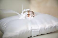 Белые и красные обручальные кольца золота на белом валике сатинировки Стоковое Фото