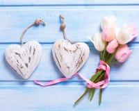 Белые и розовые тюльпаны весны и 2 декоративных сердца на сини Стоковое Изображение RF