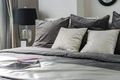 Белые и серые подушки на кровати Стоковое Изображение