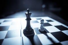 Белые и черные части на шахматной доске Стоковые Фото