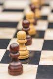 Белые и черные шахматные фигуры на доске Стоковые Изображения RF