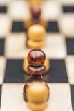 Белые и черные шахматные фигуры на доске Стоковое Фото