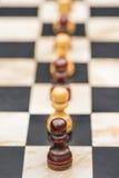 Белые и черные шахматные фигуры на доске Стоковое Изображение