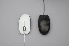 Белые и черные mouses с кабелями на сером цвете Стоковое Фото