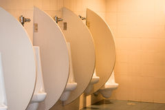 Белые керамические писсуары в комнате ` s людей Стоковые Фотографии RF