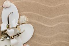 Белые кувырки с стразами и seashell на волнистом песке Стоковые Фотографии RF