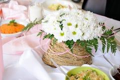 Белые маргаритки в плетеной корзине на белой таблице Стоковое фото RF
