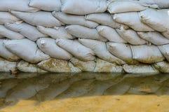 Белые мешки с песком для обороны и ее потока вода коричневого цвета отражения Стоковые Изображения RF