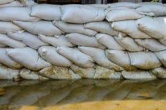 Белые мешки с песком для обороны и ее потока вода коричневого цвета отражения Стоковая Фотография RF