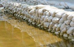 Белые мешки с песком для обороны и ее потока вода коричневого цвета отражения Стоковое Изображение