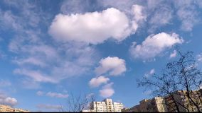 Белые облака плавают на голубое небо над домами сток-видео