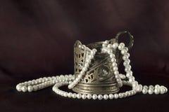 Белые ожерелье жемчуга и чашка серебра Стоковая Фотография
