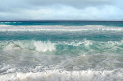 Белые пенообразные волны и постепенно затмевая цвет моря Стоковое фото RF