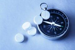 Белые пилюльки и компас аспирина Стоковые Фотографии RF