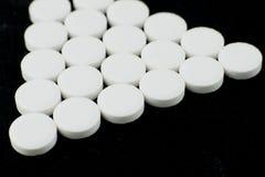 Белые пилюльки на черной предпосылке стоковое изображение