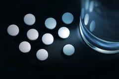Белые пилюльки помещенные около стекла воды Стоковое Фото