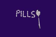 Белые пилюльки подписывают с ложкой на фиолетовой предпосылке стоковое фото