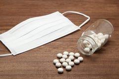 Белые пилюльки разливая из прозрачных бутылки и маски медицины на древесине Стоковые Фотографии RF