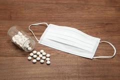 Белые пилюльки разливая из прозрачных бутылки и маски медицины на древесине Стоковое Фото