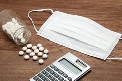 Белые пилюльки разливая из прозрачных бутылки, маски, и калькулятора медицины на древесине Стоковое Фото