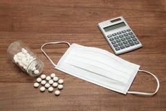Белые пилюльки разливая из прозрачных бутылки, маски, и калькулятора медицины на древесине Стоковые Фото