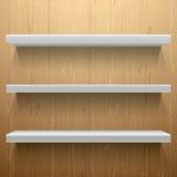 Белые полки на деревянной предпосылке Стоковое фото RF
